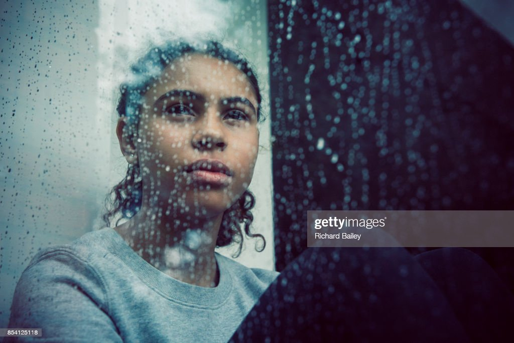 Girl staring out of rainy window : Stock Photo