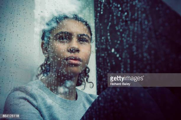 girl staring out of rainy window - sadness stock pictures, royalty-free photos & images
