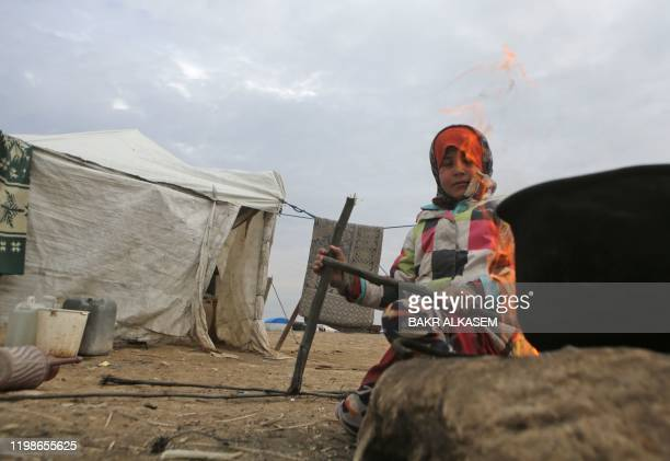 Girl starts a fire by a cooking pot outside tents where displaced Syrian families from the south of Aleppo are taking refuge, in the vicinity of the...