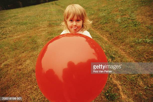 Girl (1-3) sticking out tongue behind red ball