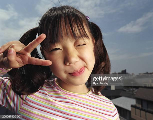 Filles (de 6 à 8) Tirer la langue, faisant signe de la paix