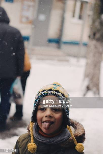 girl sticking out tongue while standing outdoors during winter - alina stock pictures, royalty-free photos & images