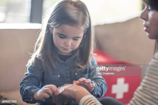girl sticking plaster onto mothers hand - first aid stock pictures, royalty-free photos & images