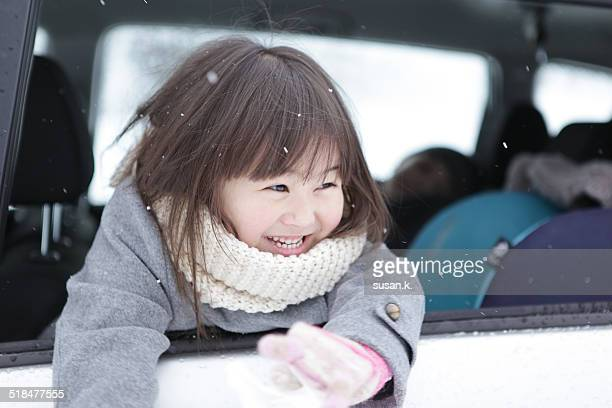 Girl sticks head & hands out of car to feel snow