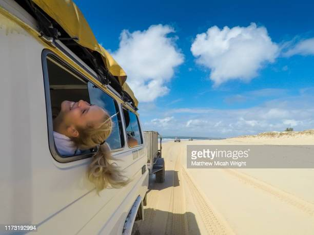 a girl sticks her head out the window as she drives down the beach. - queensland foto e immagini stock
