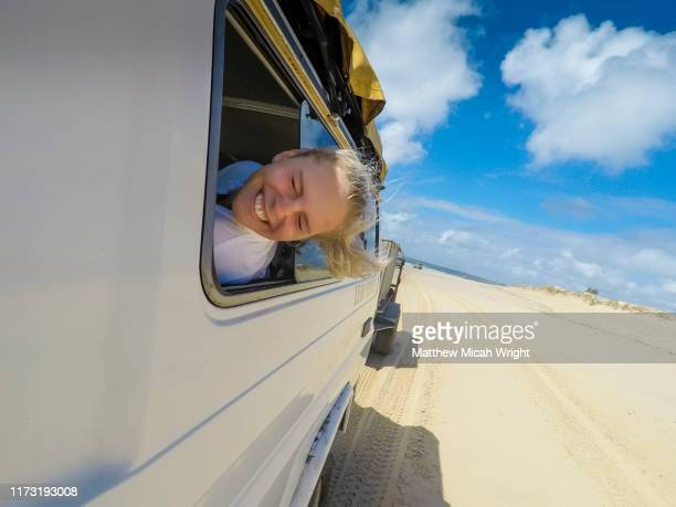 a girl sticks her head out the window - road trip stock pictures, royalty-free photos & images