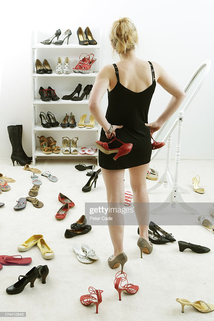 Girl stood, surrounded by shoes : Stock Photo