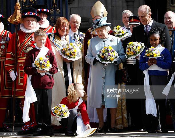 A girl stoops to pick up a paper containing the order of service for Britain's Queen Elizabeth II after the Maundy service at Derby Cathedral on...