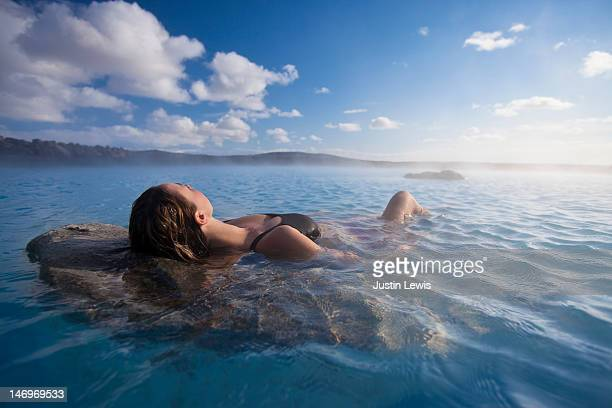 Girl stretched out on rock in ethereal hot spring