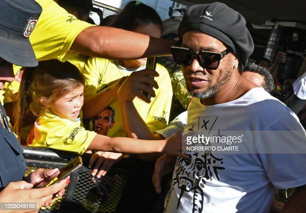 TOPSHOT A girl stretches to touch Brazilian exfootball star Ronaldinho Gaucho upon his arrival at Silvio Pettirossi International Airport in Luque...