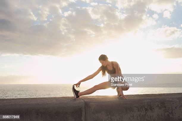 Girl stretching during workout near ocean, sunset