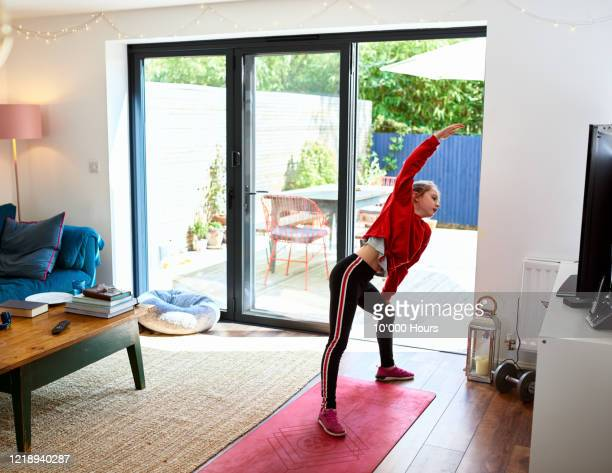 Girl stretching sideways during at home fitness class