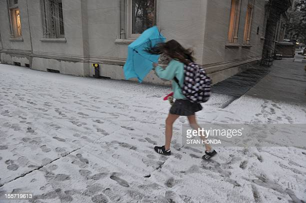 A girl struggles with an unbrella in the wind and snow on Park Avenue as a strong winter storm hits the northeast November 7 2012 in New York AFP...
