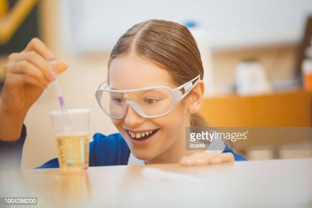 meisje student doet experiment in de klasse van de chemie - izusek stockfoto's en -beelden