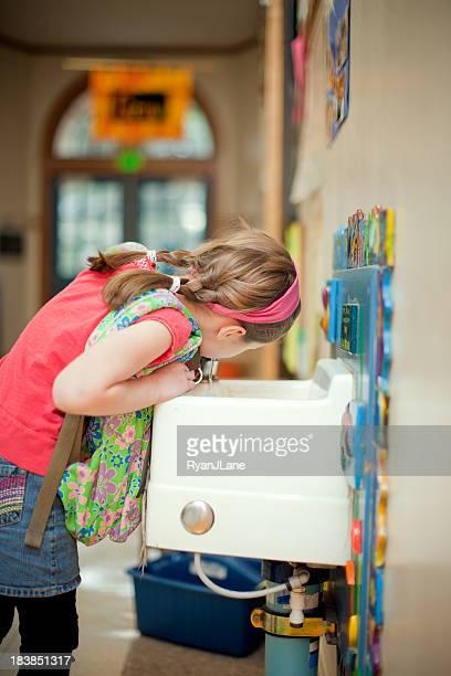 Chica estudiante en la escuela de beber de la fuente
