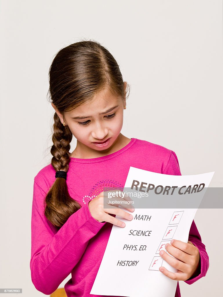 Girl student holding failing report card : Stock Photo
