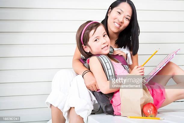 Girl student hugging mother at front steps