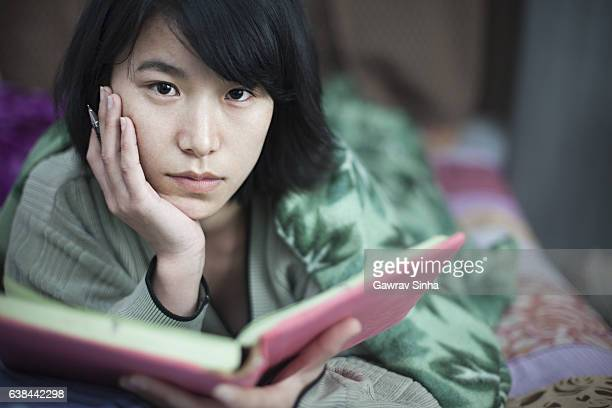 Girl student studying in bed at home.