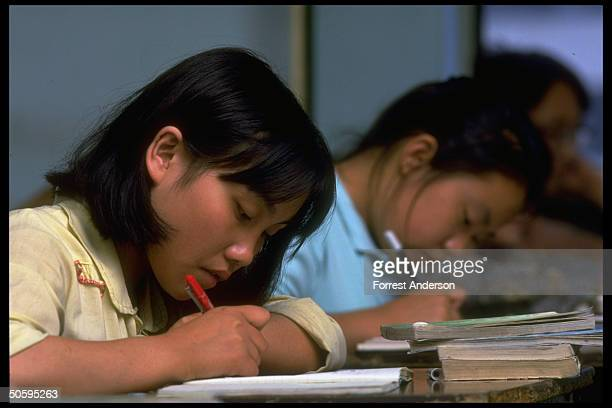 Girl students bent industriously over desks taking notes in chemistry class at Zhengze private middlehigh School