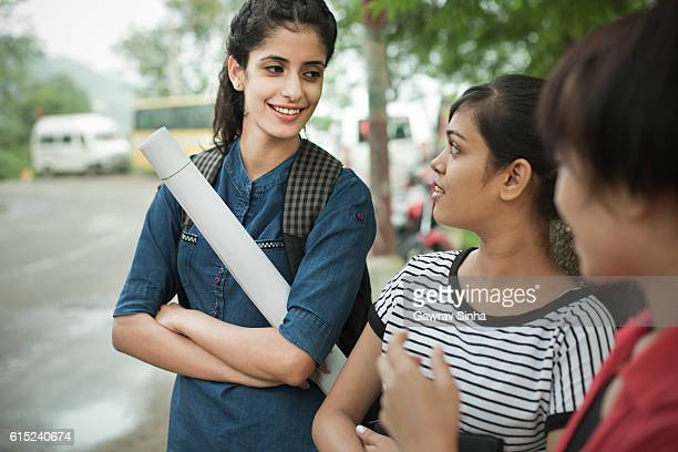 Girl students gossiping while waiting for bus by road side.