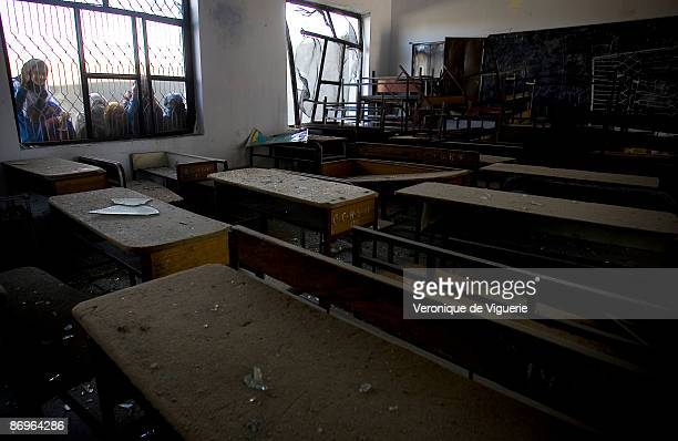 Girl students look through the window at the damage in their classroom at Hathier High School which was bombed on March 22 2009 by Taliban militants...