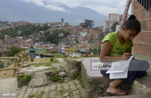 A girl studies outsid her house in the Commune 4 Moravia shantytown in Medellin Antioquia department Colombia on April 9 2014 Moravia which in 30...