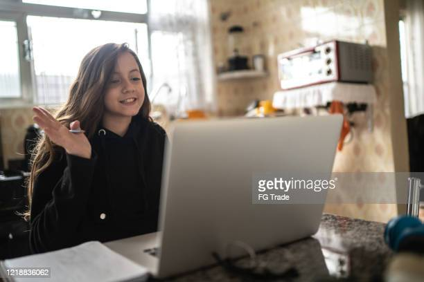 girl studying and making a video call via laptop at home - isolamento foto e immagini stock