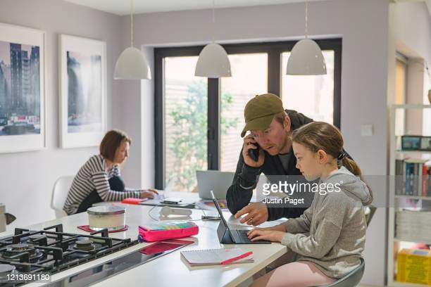 girl studying at home whilst parents work from home - assistance stock pictures, royalty-free photos & images