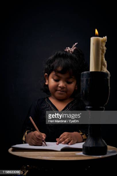 girl studying by table while sitting against black background - heri mardinal stock pictures, royalty-free photos & images