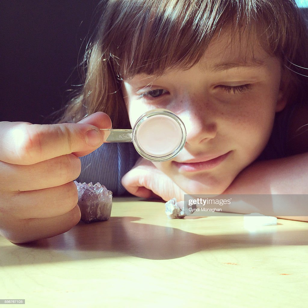 Portrait of a little girl with her chin resting on her arm looking through a magnifying glass at rocks and minerals. Childhood. Education. Science.