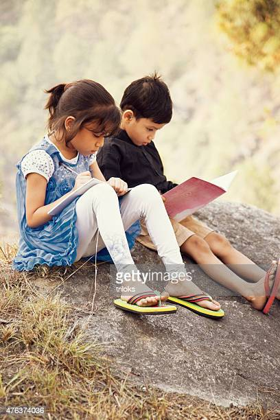 Girl studying with her brother