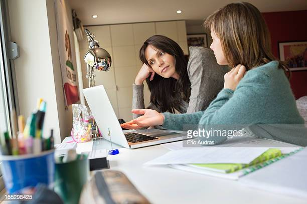 Girl studying with her mother on a laptop at home