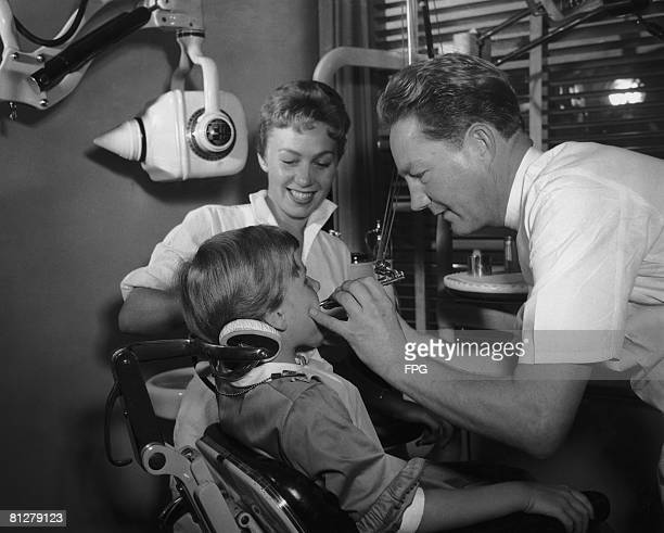 A girl submits to the ministrations of a dentist and a dental hygienist circa 1950