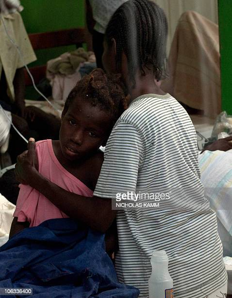 A girl suffering from cholera rests on her mother's shoulder as rain pours into the ward at the Charles Colimon hospital in Petite Riviere on the...
