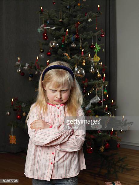 A girl sulking in front of a Christmas tree