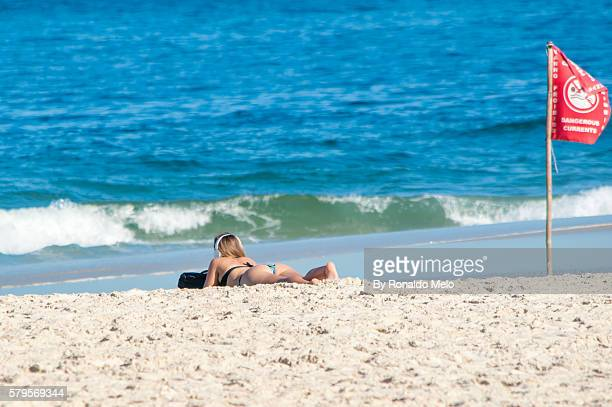 Girl sunbathing listening to music with a flag dangerous current.