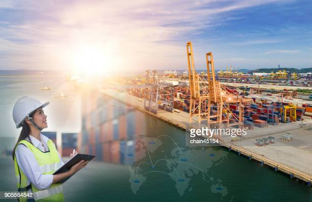 Girl supervisor worker checking transportation information of Business port with Ship for container with working crane bridge in shipyard for Logistic Import Export background in Thailand.