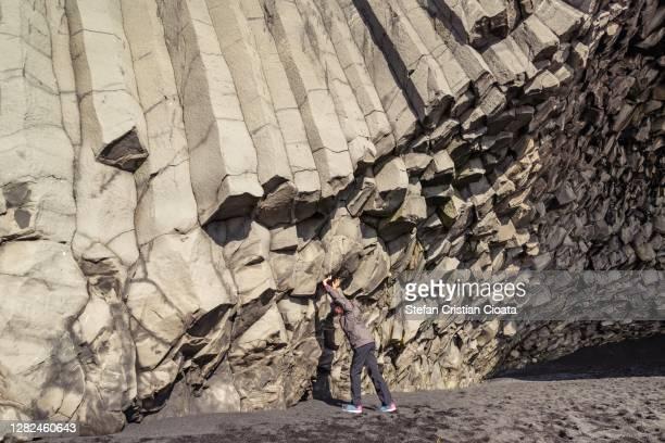 girl supports a a wall of basalt columns at halsanefshellir iceland europe - cristian neri foto e immagini stock