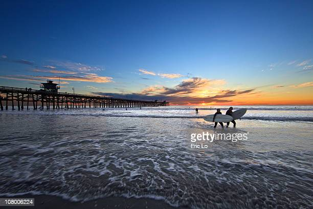 girl surfers at twilight - san clemente california stock pictures, royalty-free photos & images