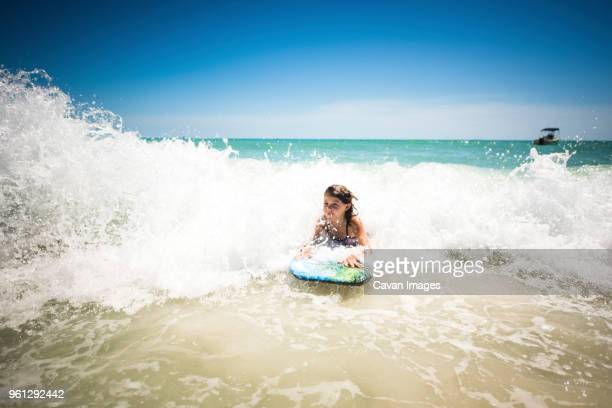 girl surfing in sea against clear sky - anna maria island stock pictures, royalty-free photos & images