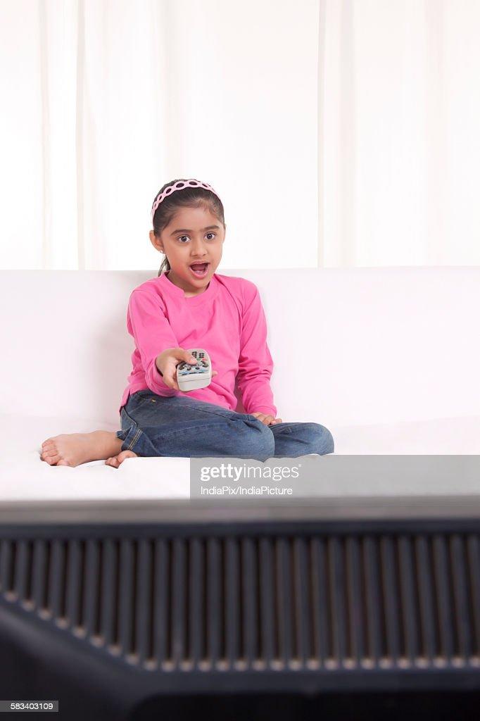 Girl surprised watching tv : Stock Photo