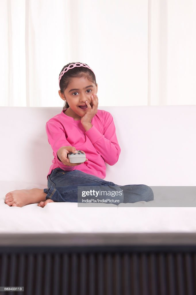 Girl surprised watching tv : Stock Photo