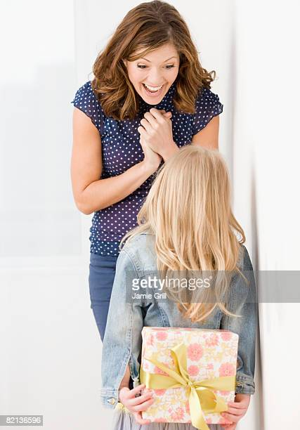 Girl surprising mother with gift