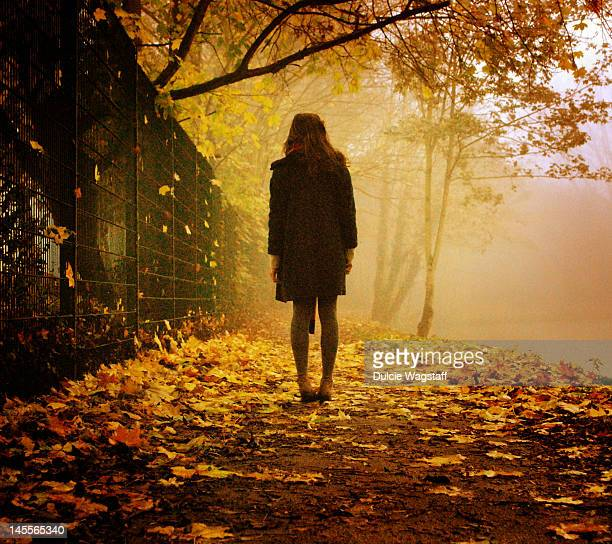 Girl surrounded by autumn leaves
