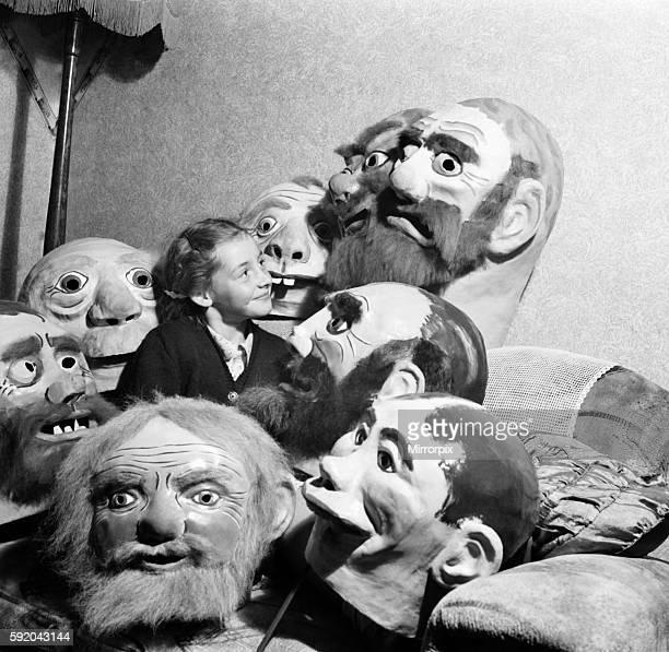 Girl surrounded by ugly masks September 1952 C4445