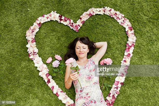 Girl  surrounded with rosepedals heart.