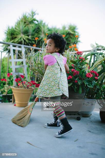 girl sweeping patio with broom - sweeping stock pictures, royalty-free photos & images
