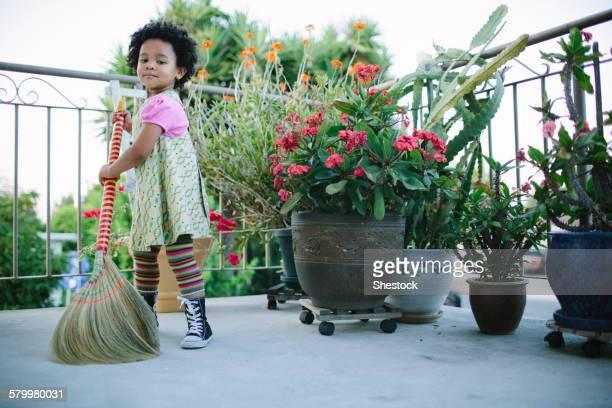 Girl sweeping patio with broom