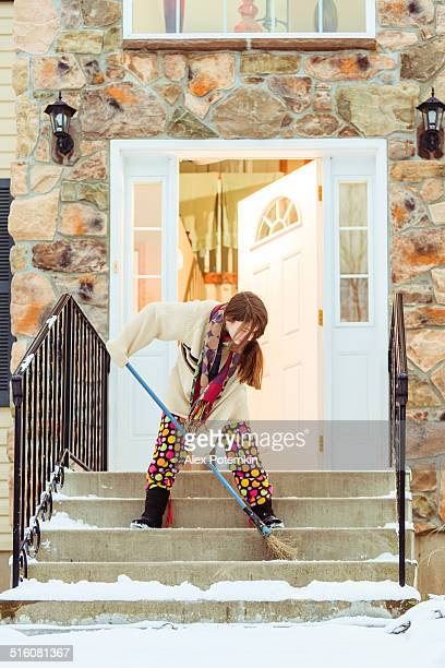 Girl sweeping snow off steps of a stone home with a broom.