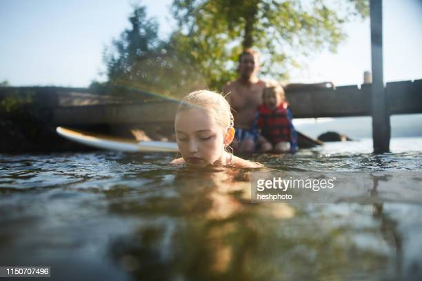 girl swimming and playing in lake, father and sister in background - heshphoto stockfoto's en -beelden